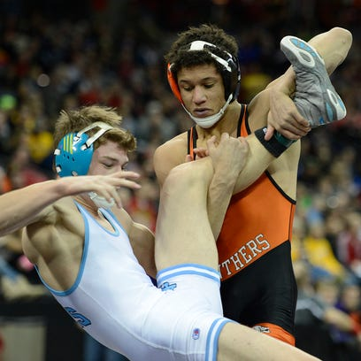 At right, Oconto Falls' Dewey Krueger takes down Wisconsin Dells' Willie Vandenlangenberg in their 152-pound Division 2 semifinal match during the WIAA individual wrestling state tournament Friday at the Kohl Center in Madison. Krueger won the match.