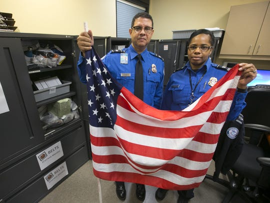 TSA Administrator Kevin Miller (left) and Lead TSA Officer Jasmon Cornick hold an American flag that was left behind at a TSA checkpoint at Phoenix Sky Harbor International Airport and is now held at the lost and found at the TSA offices at Sky Harbor.