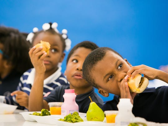 First grader Dasyr Brice (right) takes a bite of his lunch as students enjoy lunch time at Stubbs Elementary School in Wilmington. A mystery donor paid $1,200 to cover the lunch bills for all students.