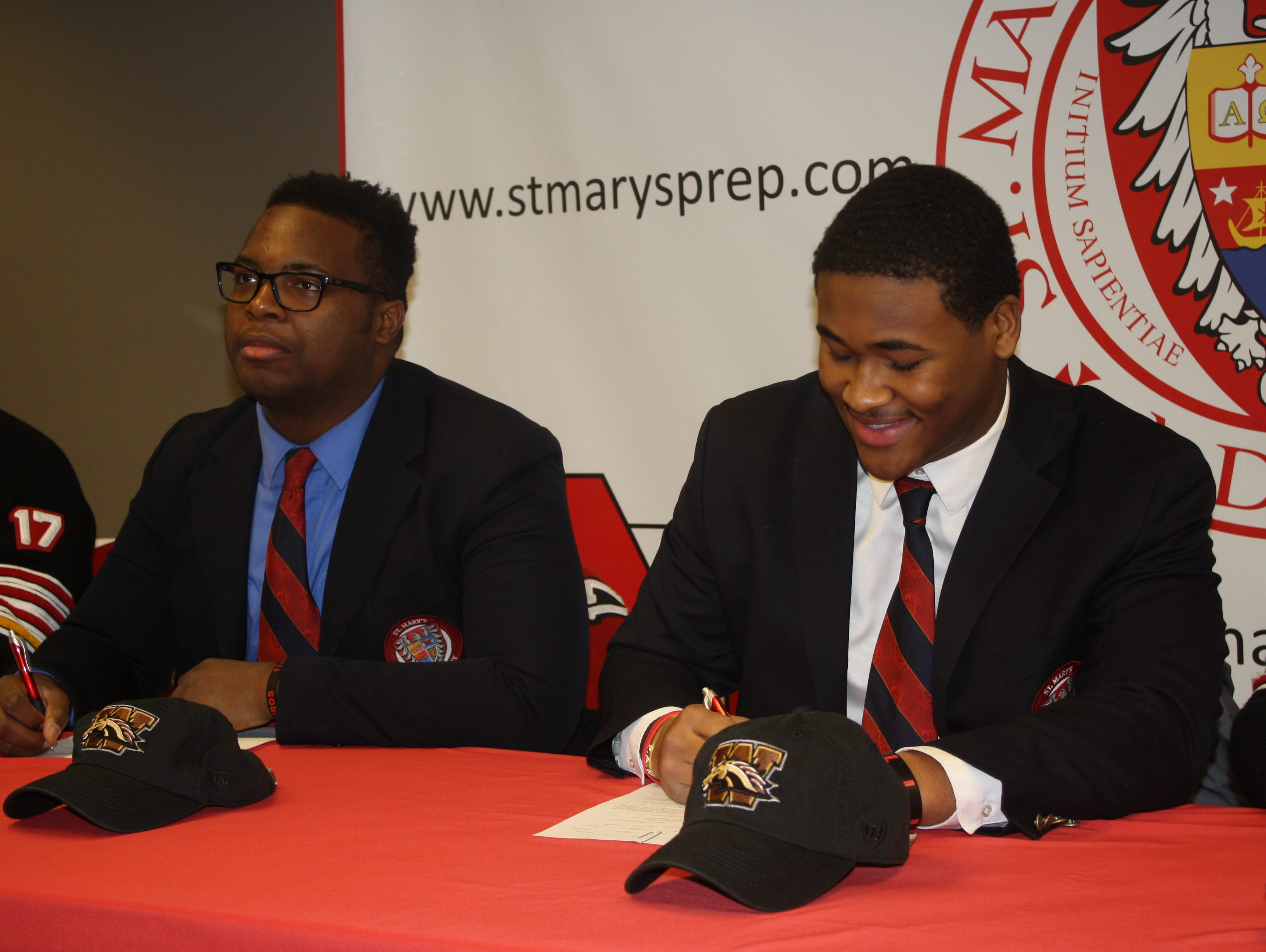 Defensive lineman Ralph Holley, left, and linebacker Dwayne Chapman III of Orchard Lake St. Mary's sign with Western Michigan on Wednesday, Feb. 1, 2017.