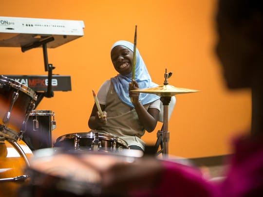 Eunayjah Thomas, 10, has fun on the drums in the recording studio at Reeds Refuge in Wilmington.