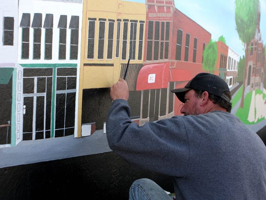 "Stacy Karnes of Howell works on a mural depicting ""old"