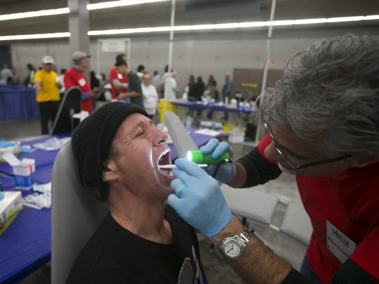Roy Ortiz of Phoenix is examined by dentist William Balestrino during the Third annual Dental Mission of Mercy event at Veterans Memorial Coliseum in Phoenix on Dec. 12, 2014.