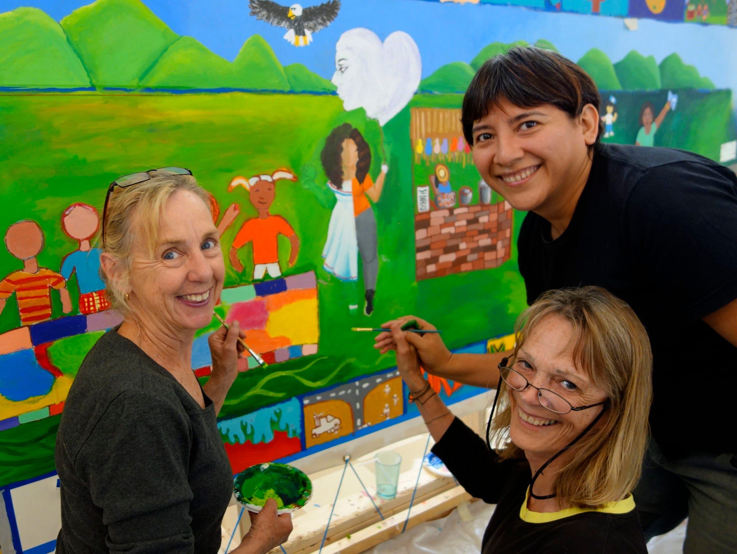 """Two community participants help paint the """"Tree of"""