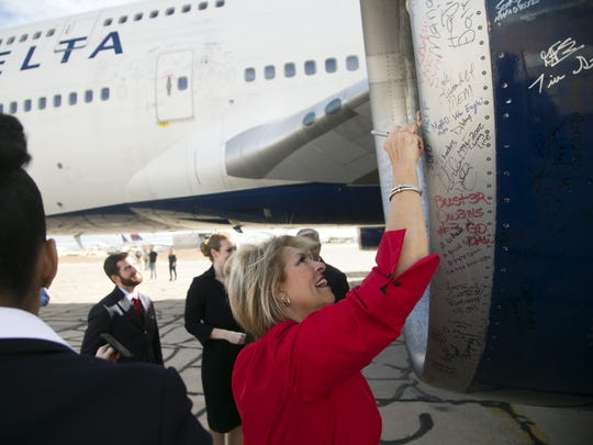 Delta flight attendant Stephanie Nelson signs a Delta 747 turbine of the what is the last 747 that Delta flew after it landed at the Pinal Airpark in Marana, for its final resting place on Wednesday, January 3, 2018.