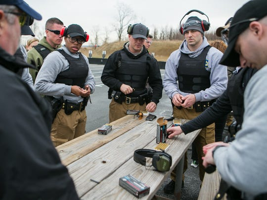 New Castle County Police recruits load their magazines before going to the firing line for their firearms training session.