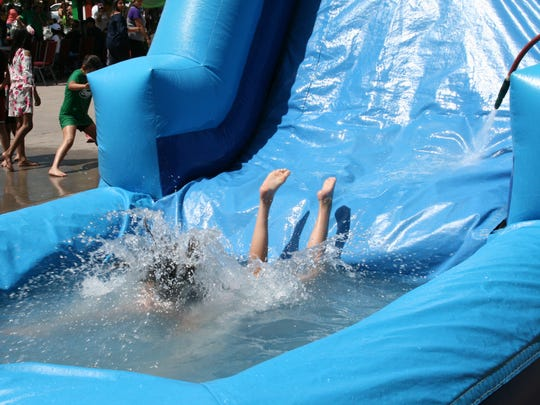 A child splashes down the waterslide at the St. George Catholic Church's Cinco de Mayo celebration on May 5, 2018.