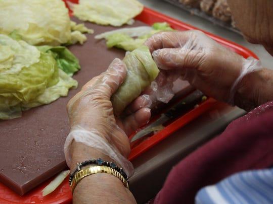 A volunteer rolls cabbage around meat to form holupki