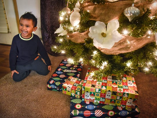 Maddox Garcia smiles while checking out presents under