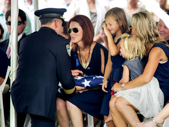 Dechia Badeaux Gerald, wife of Officer Matthew Gerald- one of three Baton Rouge law enforcement officers killed in a July 17 shootout- accepts the American flag as their daughter, Dawclyn, becomes emotional at his internment in Zachary July 22.