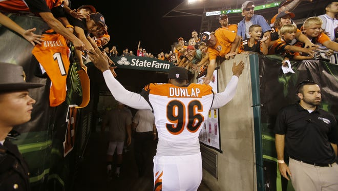 Cincinnati Bengals defensive end Carlos Dunlap (96) gives high fives to fans after the preseason NFL game between the New York Giants and the Cincinnati Bengals, Friday, Aug. 14, 2015, at Paul Brown Stadium in Cincinnati, Ohio.