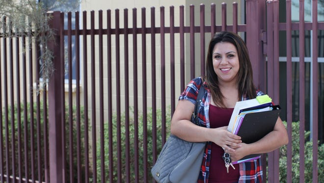 Zahide Betancourt, 28, holds her textbooks in front of Wilson Community Center in Phoenix, where she takes a GED prep course