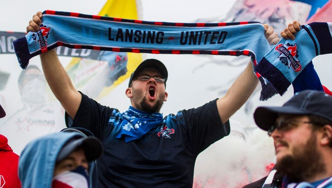 Jeff Backoski holds up a Lansing United scarf and shouts at the start of the NPSL Home Opener against FC Indiana May 19. Backoski is a member of Sons of Ransom, the supporters group for Lansing United.