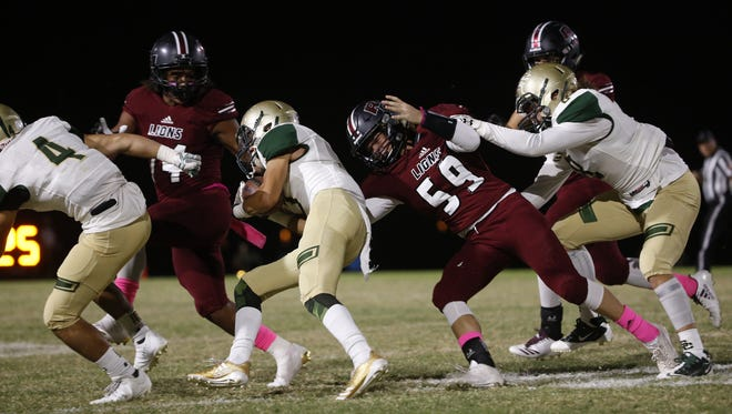 Red Mountain's Braydon Janzen (59) tackles Skyline's Cole Lopez (3) at Red Mountain High School in Mesa, Ariz. on October 20, 2017.