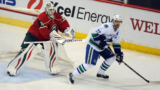 Minnesota Wild Goalie Darcy Kuemper (35) clears Vancouver Canucks forward Daniel Sedin (22) from his crease in the third period at Xcel Energy Center.