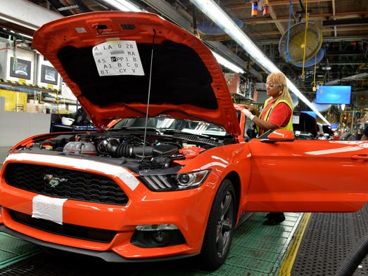 A worker applies touches to a new Ford Mustang. Production officially starts today in Flat Rock, Mich.
