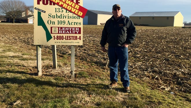 Jaymes Lester stands beside a sign advertising his land to sale to a developer in February.
