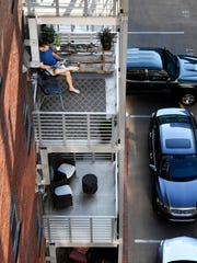 "Derek Brooks sits on the balcony of his Printers Alley condo July 2, 2018, in Nashville. ""It's a great location in the middle of everything, far enough from Broadway not to hear anything but close enough to walk over,"" says Brooks, the executive chef at the Hermitage Hotel's Capitol Grille, a posh farm-to-table restaurant just a few blocks west."