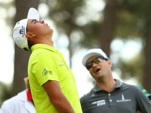 Rickie Fowler reacts after his tee shot with Zach Johnson