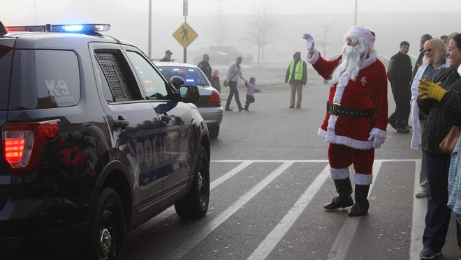 Santa and onlookers greet the more than 100 Livingston County children ages 4-12 and their law enforcement partners at the Genoa Township Walmart for shopping during the 13th annual Shop with a Cop program on Saturday.