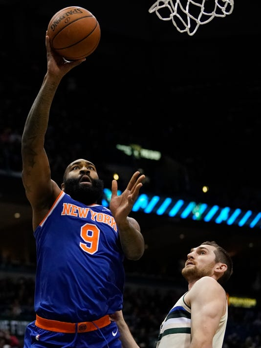 New York Knicks' Kyle O'Quinn shoots over Milwaukee Bucks' Tyler Zeller during the first half of an NBA basketball game Friday, March 9, 2018, in Milwaukee. (AP Photo/Morry Gash)