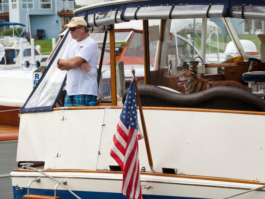 Ron Sherman of Detroit stands on the back of his Chris Craft commander with his dog, Commander, during the Blue Water Classic and Antique Boat Show Saturday at the River Street Marina in Port Huron.