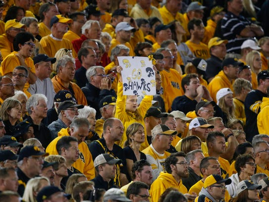 A young Iowa Hawkeye fan holds a poster up against
