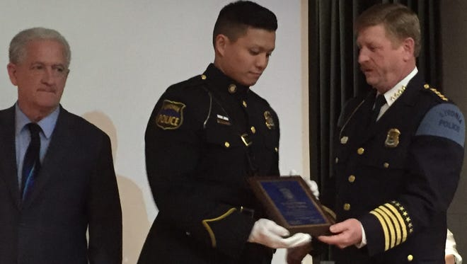 Livonia Police Chief Curtis Caid, right, hands Officer Tony Dang a police department Lifesaving Award Tuesday evening as Mayor Dennis Wright looks on.