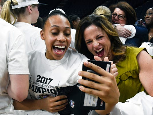 Quinnipiac guard Brittany Martin, left, and Becky Mella call Martins' sister Jasmine after Quinnipiac won theNCAA college championship basketball game in the Metro Atlantic Athletic Conference tournament on Monday, March 6, 2017, in Albany, N.Y. (AP Photo/Hans Pennink)