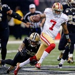 San Francisco 49ers quarterback Colin Kaepernick (7) carries past New Orleans Saints strong safety Kenny Vaccaro (32) in the first half of Sunday's game.