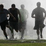 Runners go through a sheet of water from a fire truck as they take off from the starting line during the inaugural Chief's Challenge at Fairgrounds Park on Saturday, April 23, 2016.