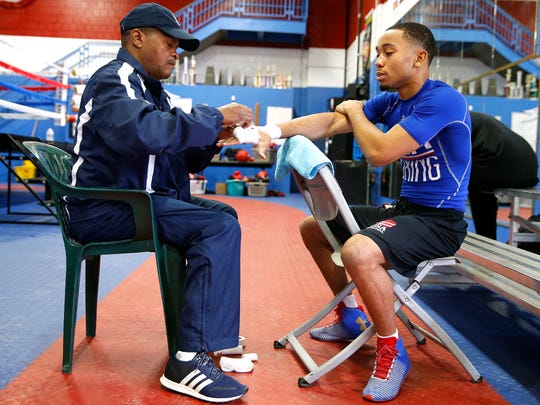 Coach Leroy Carter, Jr., tapes the hands of Duke Ragan, 19, before he trains at the Cincinnati Golden Gloves boxing gym in Over-the-Rhine Wednesday May 3, 2017. Ragan is heading to Colorado next week to train with the U. S. Olympic team.