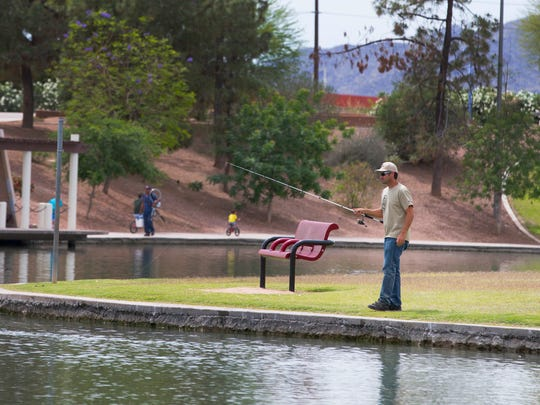 Nathan Foreman, of Queen Creek, fishes at Kiwanis Park in Tempe.