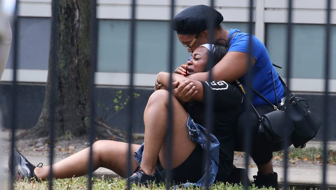 In this Sunday, Aug. 5, 2018 photo, two women cry outside the Stroger Hospital in Chicago after they were asked to leave due to overwhelming crowds of family and friends of shooting victims. Police Superintendent