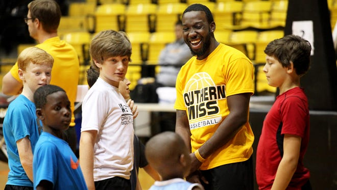 Southern Miss junior point guard Khari Price interacts with youngsters during a youth basketball camp at Reed Green Coliseum. Price sat out last season after transferring from Dayton.