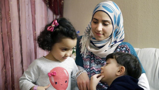 FILE - Syrian refugee Maryam al Jaddou, center, looks on as her children twins Maria, left, and Hasan, sit with her at their apartment in Dallas. The 30-year-old al Bashar al Jaddou decided to leave Syria in 2012 after his familyís home in Homs was bombed and there was nowhere safe left to live.