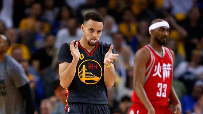 Stephen Curry #30 of the Golden State Warriors reacts after making a basket in the first quarter of their game against the Houston Rockets at ORACLE Arena on February 9, 2016 in Oakland, California.