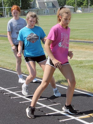 Emily Eggiman, in pink, leads Addi Clark and Nevyah Lewis through a hopscotch agility drill during outdoors weight training on Tuesday at Kewanee High School Stadium under Stage 1 guidelines.