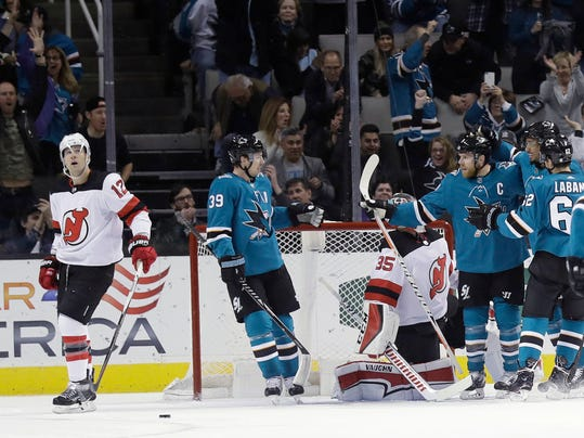 San Jose Sharks' Joe Pavelski, third from right, is hugged by teammates after scoring against the New Jersey Devils during the first period of an NHL hockey game Tuesday, March 20, 2018, in San Jose, Calif. (AP Photo/Marcio Jose Sanchez)