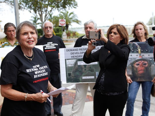 Animal rights activist Madeleine Doran, left, speaks during a Hendry County monkey farms protest outside the Harborside Event Center in Fort Myers Monday.