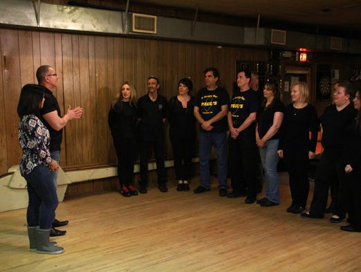 "TV host Robert Irvine, left, and Cheryl Torrenueva, designer, talk to the staff of Paul's Bar and Bowling in Paterson NJ during the filming of Food Network's ""Restaurant: Impossible."""