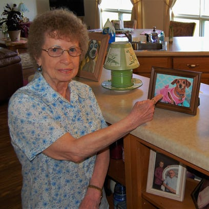 Joyce Farrey keeps several pictures of Heather, her 16-year-old dachshund, on display on her kitchen counter. Heather was killed by a deer in Farrey's backyard on the evening of May 31.