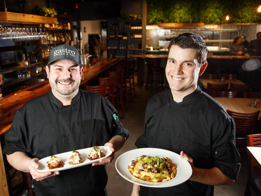 Adam Berg holds pork belly tostones and Sean Gleason