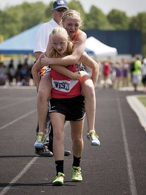 Chloe Gruenke is carried to the finish line by her twin sister, Claire, after Chloe fell to the track in pain at a state meet.