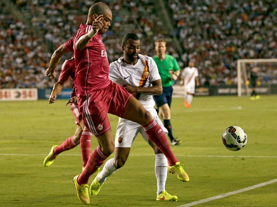 Real Madrid defender Pepe, front, clears the ball away under pressure from Roma's Ashley Cole, right, in the first half of a Guinness International Champions Cup soccer tournament match, Tuesday, July 29, 2014, in Dallas. (AP Photo/Tony Gutierrez)