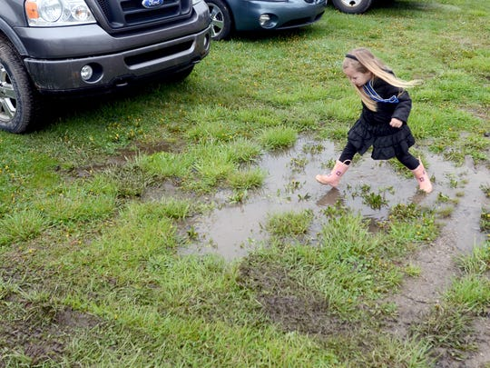 Christine Adams, 4, of Adair, plays in the muddle puddles Sunday, May 1, during Adair's annual Suckerfest.