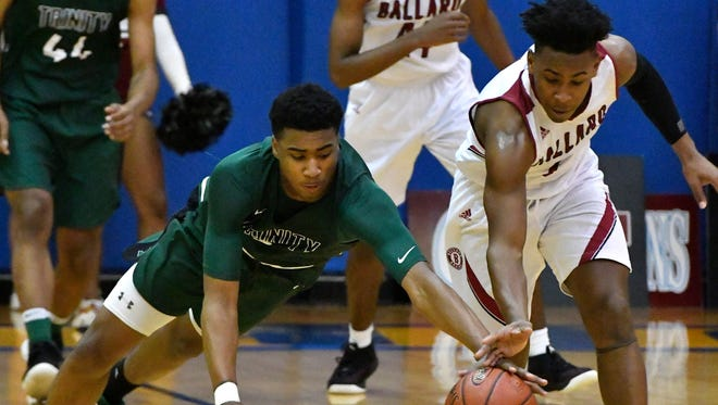 Trinity guard Jay Scrubb (4), left, battles Ballard forward Marshon Ford (2) for a loose ball during the first half of their 7th region championship game, Monday, March 5, 2018 in Louisville Ky.