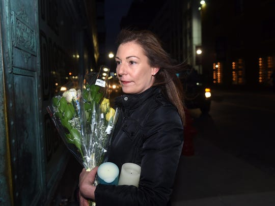 Julie Webber holds flowers and candles in rememberance of Chris Cornell outside the Fox Theatre in tribute to Chris Cornell on Friday, May 19, 2017.