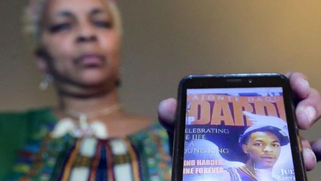 "Tracy Dardie-Clay plays a video of her cousin reciting ""The Streets,"" a poem Dardie-Clay wrote about her son's death."