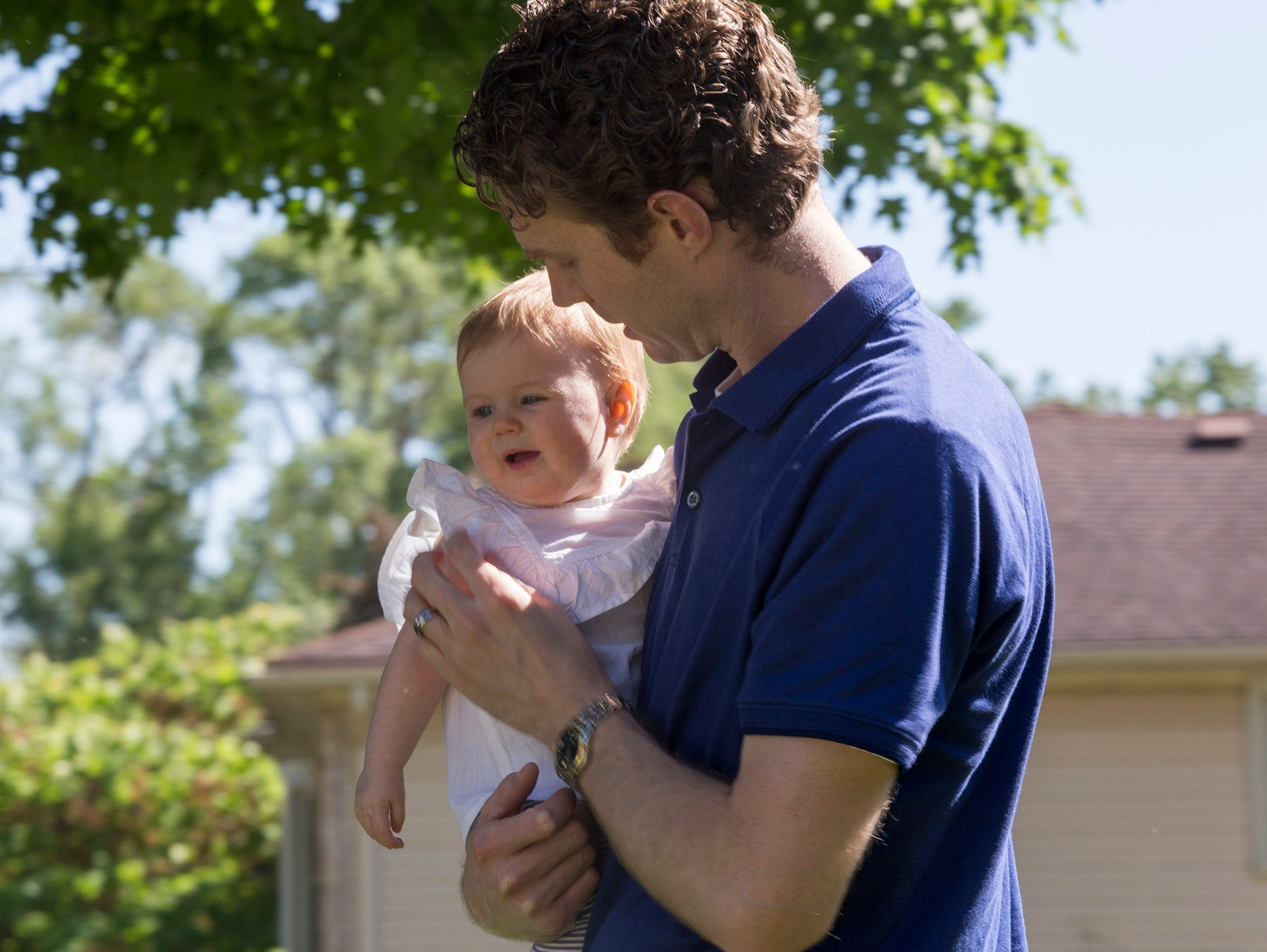 Phil Guster holds his 7-month-old daughter, Amelia